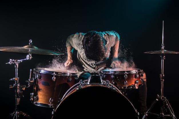 Musicista che suona la batteria con spruzzi, sfondo nero con bella luce soffusa, gioco emotivo, concetto di musica