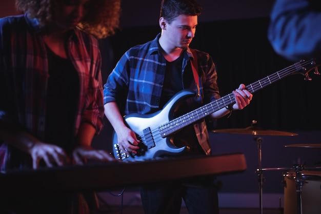 Музыкант играет на электронной гитаре в студии