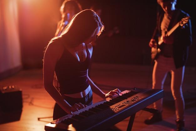 Музыкант играет на электронном пианино в студии