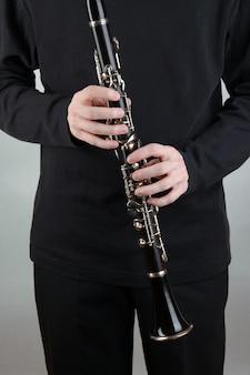 灰色のクラリネットで演奏するミュージシャン
