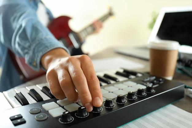 Музыкант играет на электрогитаре и миди-клавиатуре, крупным планом