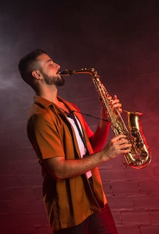Musician playing the saxophone in fog