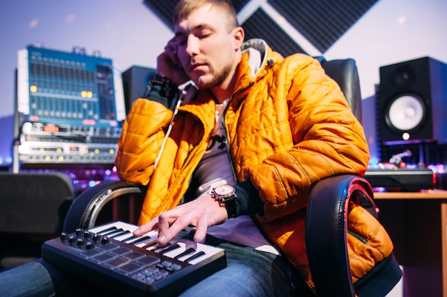 Musician playing synthesizer in recording studio