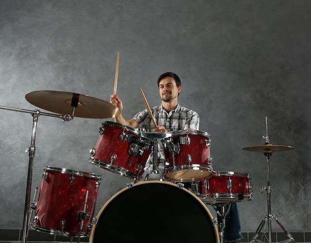 Музыкант играет на барабанах в студии