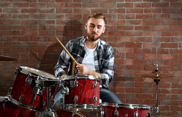 Музыкант играет на барабанах на фоне кирпичной стены