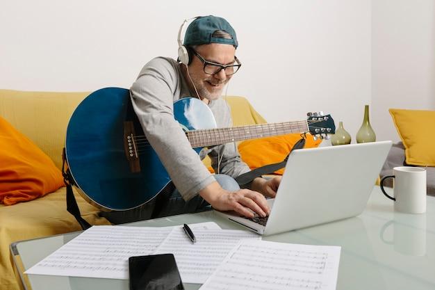 기타를 연주하고 노트북을 통해 화상 회의를 통해 동료와 음악을 작곡하는 음악가