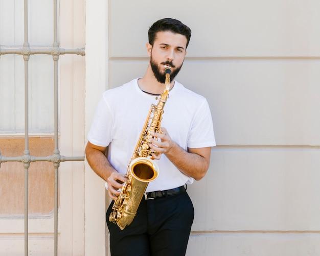 Музыкант играет на саксофоне и смотрит в камеру