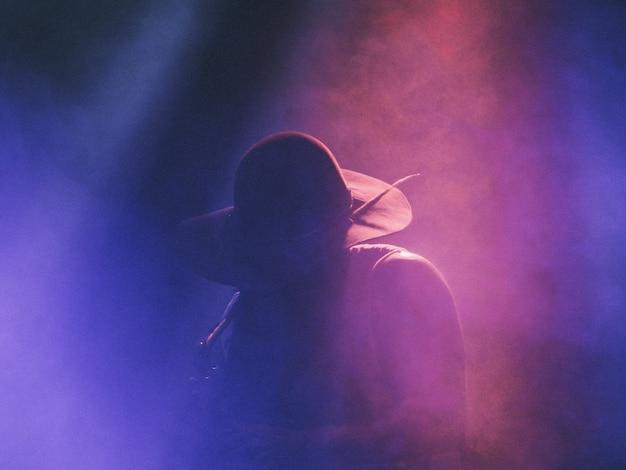 暗いスモーキーステージのクラブでのコンサートでサックスを演奏するミュージシャン
