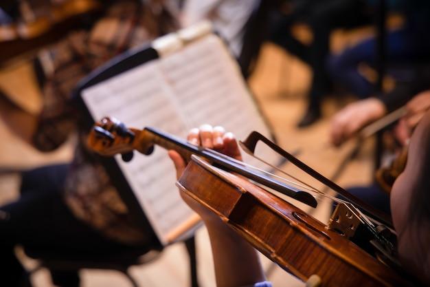 바이올린을 연주하고 클래식 음악 콘서트 도중 악보를 읽는 음악가를 닫습니다.