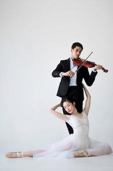 Музыкант играет на скрипке и балерина позирует
