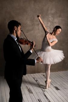 Musician playing violin and ballerina dancing