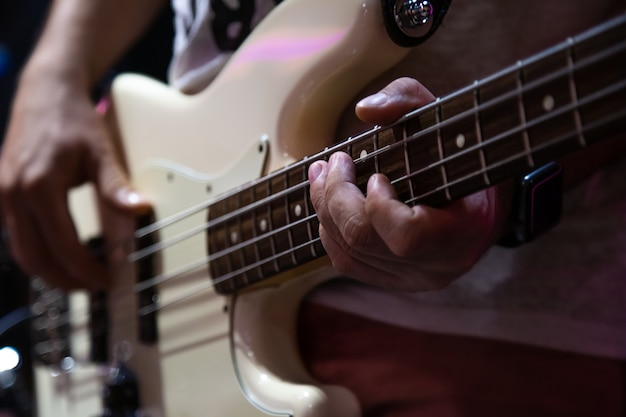 Musician playing white bass guitar close up.