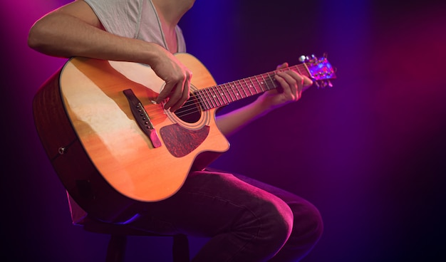 The musician plays an acoustic guitar.