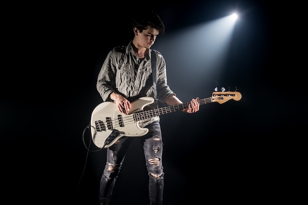 The musician plays bass guitar, on a black background with a beam of light, emotional play, music concept