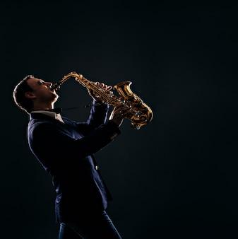 Musician plays jazz at saxophone. dark