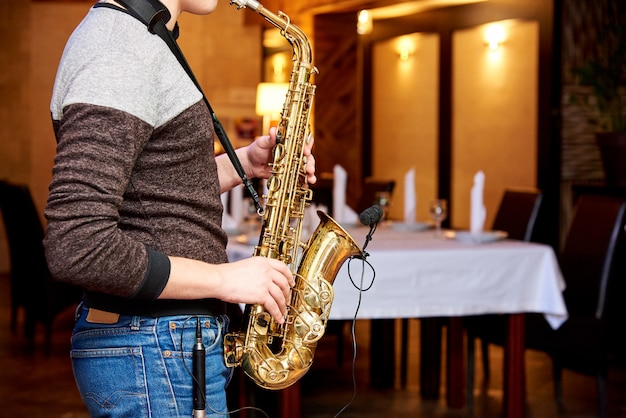 The musician plays the saxophone in a cozy restaurant.