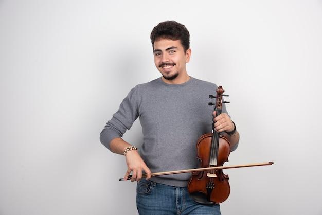 Il musicista suona il violino e sembra ispirato e positivo.