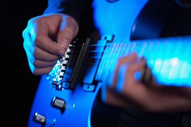 青いギターを弾くミュージシャンロックギタリスト