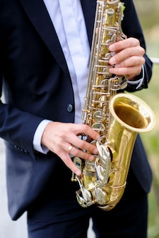 Musician in suit is playing saxophone