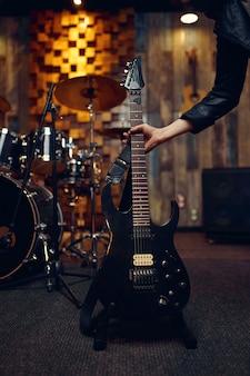 ミュージシャンはエレキギターを取り、音楽はステージで演奏します。ロックバンドの演奏またはガレージでの繰り返し、弦楽器を持った男、ライブサウンド