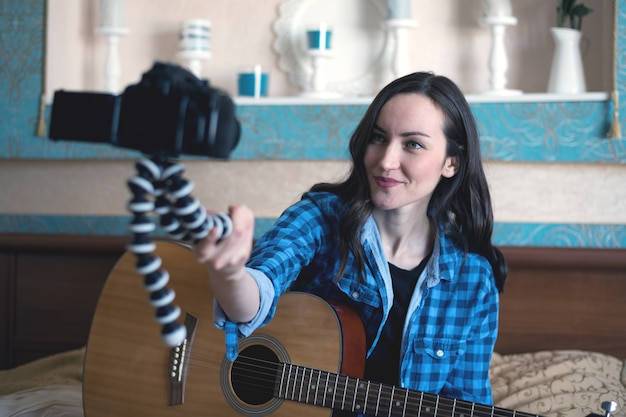 Musician with acoustic guitar on bed records herself