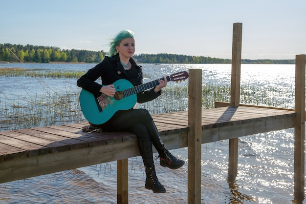 A musician with blue hair and a blue guitar sits on a lake footbridge and plays music.