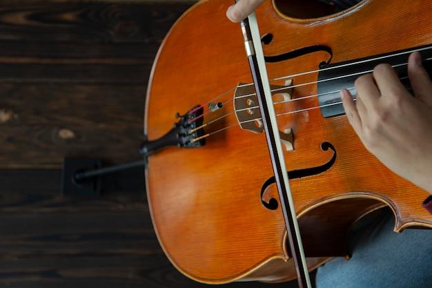 Музыкант с виолончелью играет на струнах