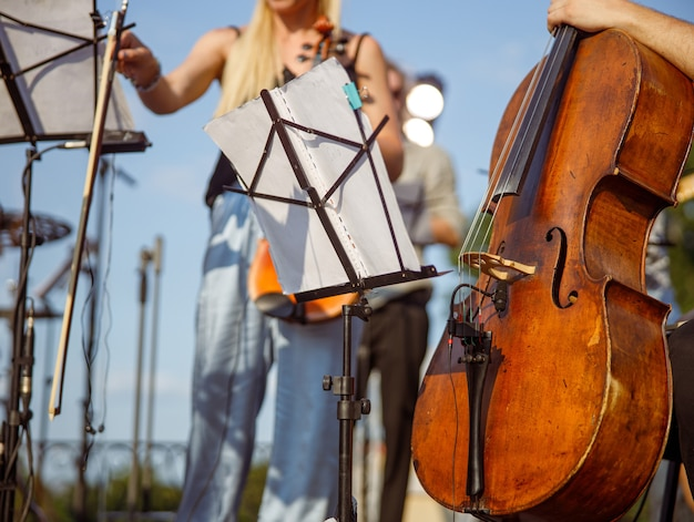 Музыкант с виолончелью сидит возле нотной стойки