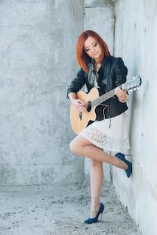 アコースティックギターと赤い髪のミュージシャンの若い女性