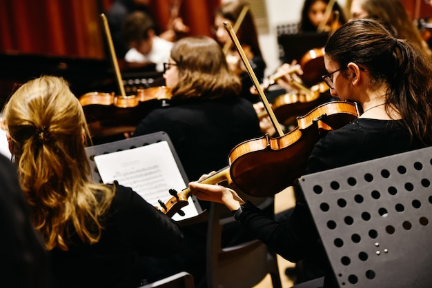 Musicians during a classical music concert, playing violins.