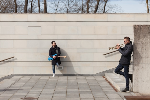 Musicians leaning on wall and playing
