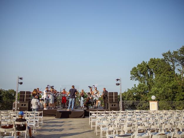 Музыканты исполняют классическую инструментальную музыку на открытой сцене