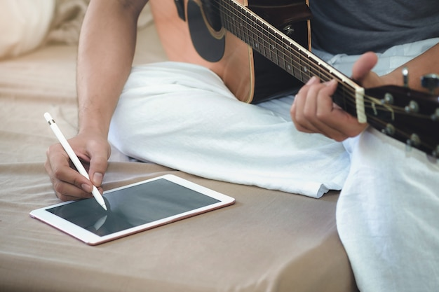 음악가는 태블릿을 사용하여 기타를 연주하고 노래를 작곡합니다.