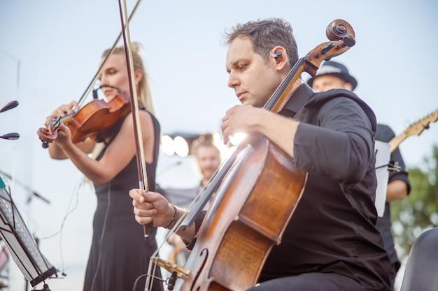 Музыканты играют классическую инструментальную музыку на улице