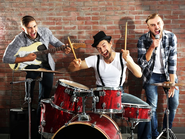 Musicians playing the drums on brick wall