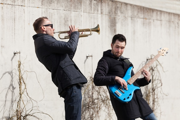Musicians playing in front of a concrete wall