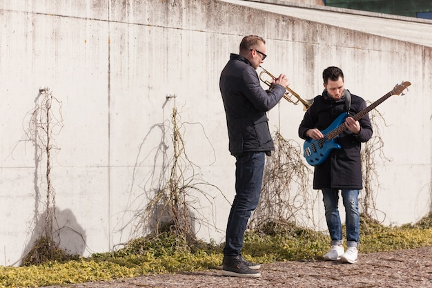 Musicians playing in front of a wall
