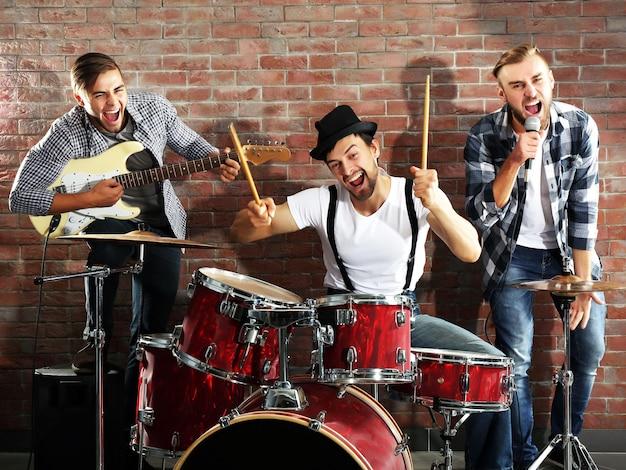 レンガの壁でドラムを演奏するミュージシャン
