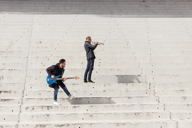 Musicians rehearsing on concrete stairs