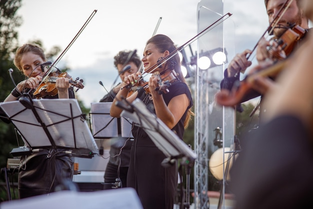 Musicians standing near music stands with notes and playing violin on outdoor stage