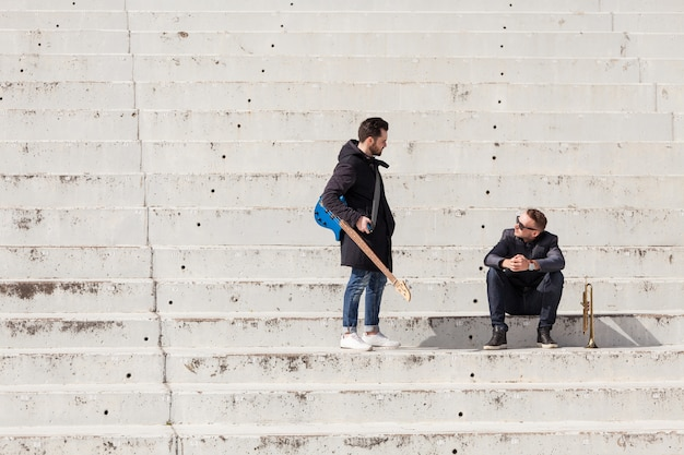 Musicians talking on concrete stairs