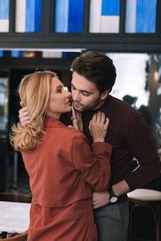 Musing beautiful woman touching man and murmuring