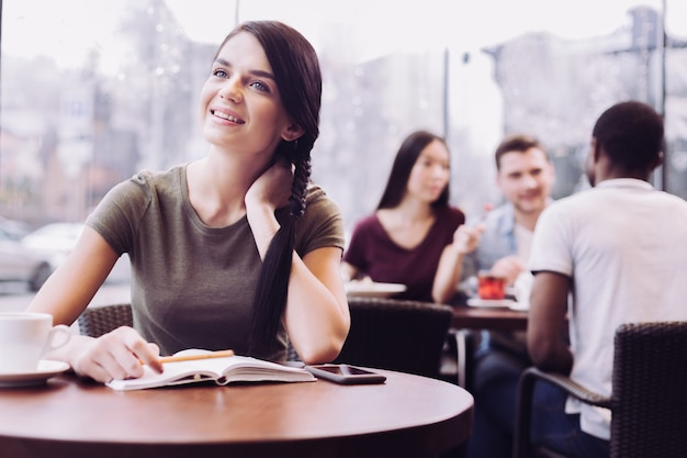 Musing dreamful female student sitting at cafe while staring up and touching her neck