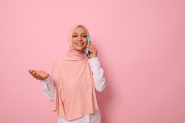 Арабская мусульманская красивая женщина с покрытой головой в розовом хиджабе разговаривает по мобильному телефону и жестикулирует руками, показывая ладонь на место для копирования. изолированный портрет на розовом пастельном фоне для рекламы