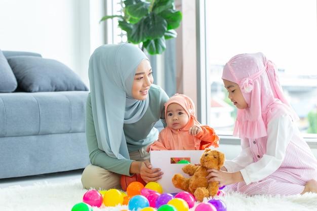 イスラム教徒のアラブの家族の母親と彼女の子供たちは、キュートで素敵な家で一緒に遊んで幸せです