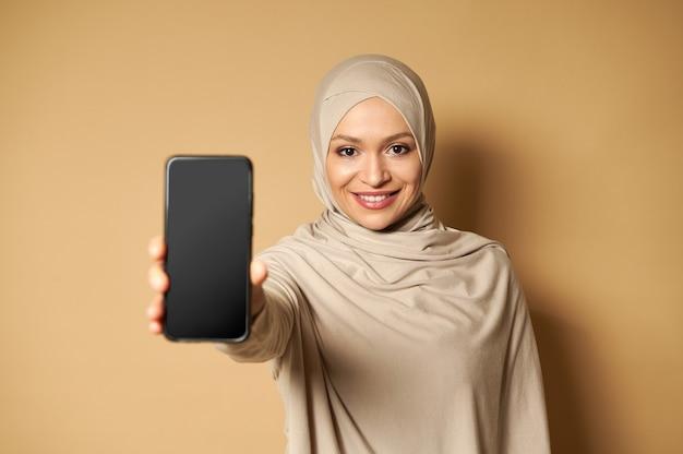 スカーフで覆われた頭を持つイスラム教徒のアラブの女性は歯を見せる笑顔で微笑んで、コピースペースでベージュの表面に立っている正面に携帯電話を示しています