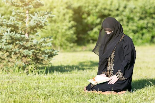 草の上に座って神に祈るイスラム教徒のアラビア語の女の子