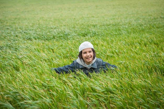 緑の美しい牧草地に立つムスリムのアラビアの子供