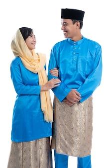 白い背景の上のハリラヤイードムバラク中のイスラム教徒のアジアのカップル
