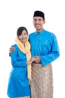 Мусульманская азиатская пара во время хари райя ид мубарак на белом фоне